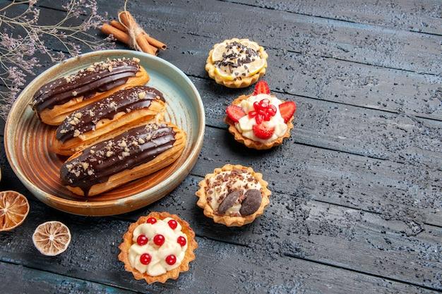 Vista inferior de éclairs de chocolate em uma placa oval cercada por tortas de limão seco e canela no lado esquerdo da mesa de madeira escura com espaço de cópia