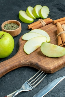 Vista inferior de fatias de maçã e paus de canela na faca e garfo de menta seca em pó em uma tigela pequena na mesa escura
