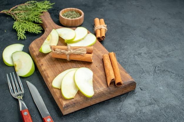 Vista inferior de fatias de maçã e paus de canela na tábua de madeira. faca e garfo em pó de hortelã seca em uma tigela pequena na mesa escura com espaço livre