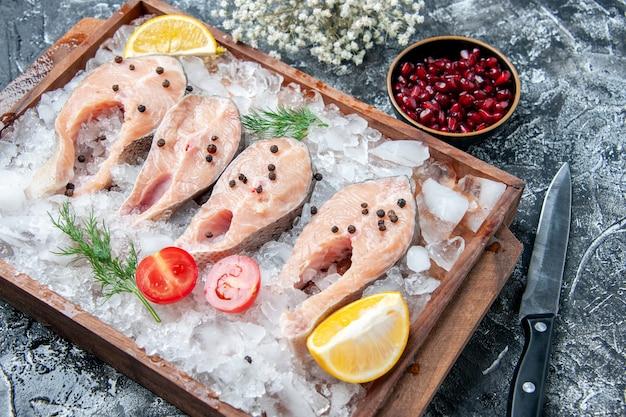 Vista inferior de fatias de peixe cru com gelo em sementes de romã em tabuleiro de madeira em uma faca pequena tigela na mesa