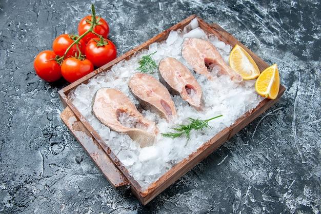 Vista inferior de fatias de peixe cru com gelo em um galho de tomate em tábua de madeira