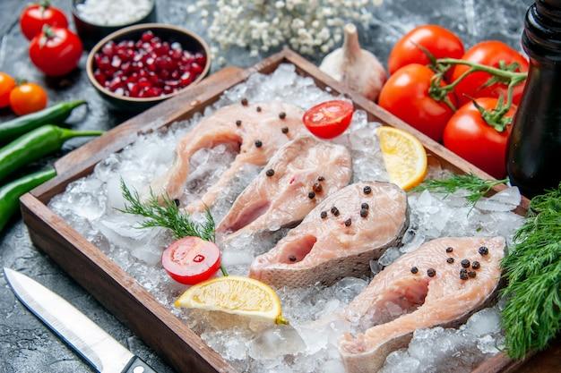 Vista inferior de fatias de peixe cru com gelo rodelas de limão em tigelas de tábua de madeira com sementes de pemagranato e sal marinho na mesa