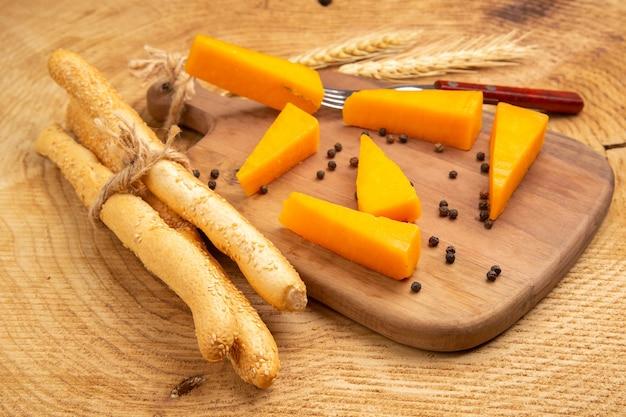 Vista inferior de fatias de queijo espalhado com pimenta do reino e garfo na tábua de trigo espiga pão na mesa de madeira