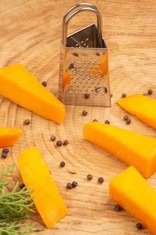 Vista inferior de fatias de queijo espalhado com ralador de pimenta preta na mesa de madeira
