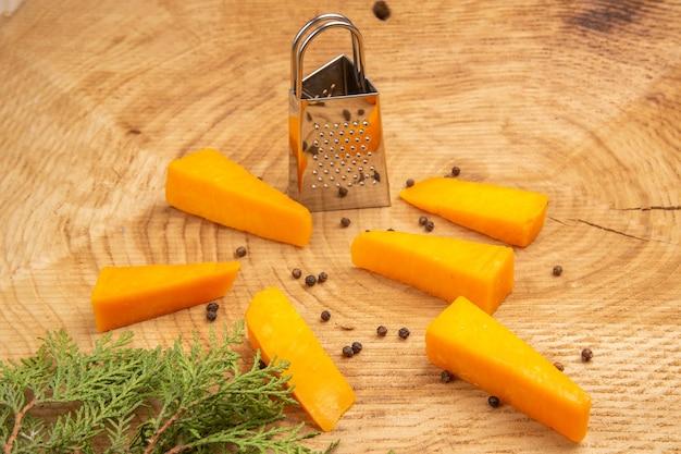 Vista inferior de fatias de queijo espalhado em caixa de pimenta preta ralador de galho de árvore de pinho na mesa de madeira