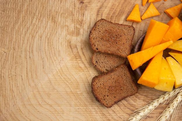 Vista inferior de fatias de queijo, fatias de pão e trigo espiga na mesa de madeira