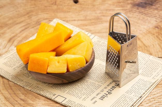 Vista inferior de fatias de queijo no ralador de caixa de tigela no jornal na mesa de madeira