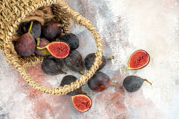 Vista inferior de figos frescos espalhados da cesta em um fundo nu