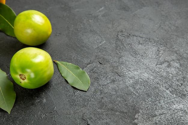 Vista inferior de folhas de louro com tomates verdes em fundo escuro