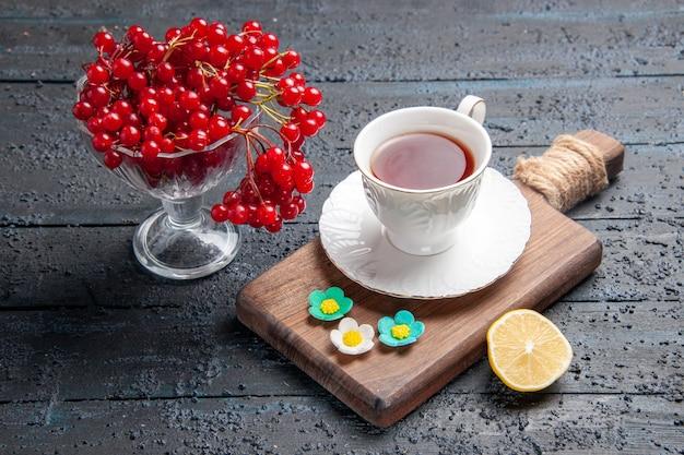 Vista inferior de groselha em um copo, uma xícara de chá em uma tábua de cortar, uma fatia de limão no fundo escuro