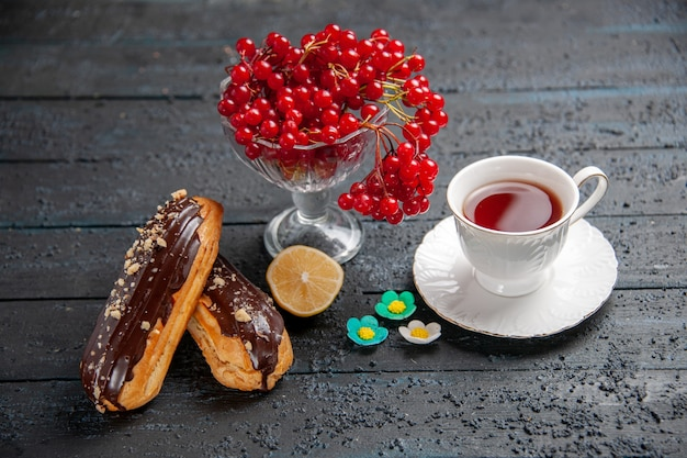 Vista inferior de groselha em um copo, uma xícara de chá, fatia de limão de éclairs de chocolate em fundo escuro