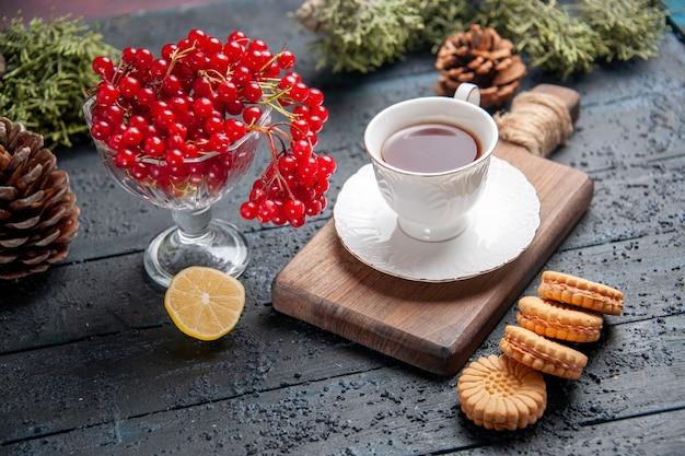 Vista inferior de groselha em um copo, uma xícara de chá na tábua de cortar uma fatia de pinhas de limão e biscoitos na mesa de madeira escura