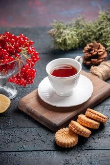 Vista inferior de groselha em um copo, uma xícara de chá na tábua de cortar uma fatia de pinhas de limão e biscoitos no fundo escuro de madeira