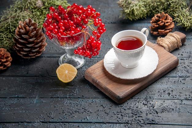 Vista inferior de groselha em um copo, uma xícara de chá na tábua de cortar uma fatia de pinhas de limão no fundo escuro de madeira