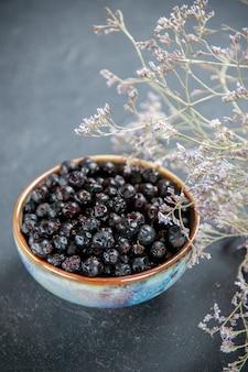 Vista inferior de groselha preta em uma tigela de flores secas em superfície isolada