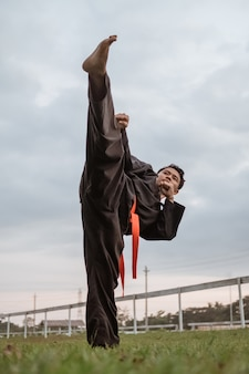 Vista inferior de homens usando uniformes de silat pencak com chutes