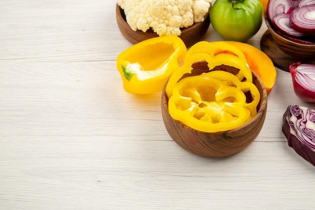 Vista inferior de legumes frescos cortados cebola, pimentões amarelos em tigelas na mesa de madeira branca com espaço livre