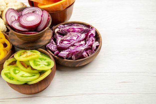 Vista inferior de legumes picados, corte de repolho roxo, corte de abóbora, corte de cebola, corte de tomates verdes em tigelas na mesa branca com espaço de cópia
