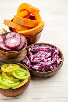 Vista inferior de legumes picados, corte de repolho roxo, corte de abóbora, corte de cebola, corte de tomates verdes em tigelas na mesa branca
