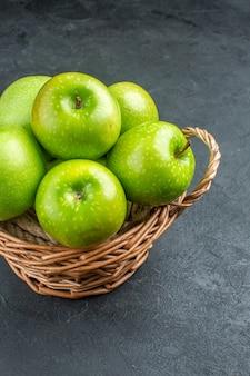 Vista inferior de maçãs frescas em uma cesta de vime em superfície escura