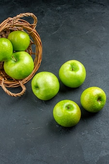 Vista inferior de maçãs frescas espalhadas de uma cesta de vime na superfície escura