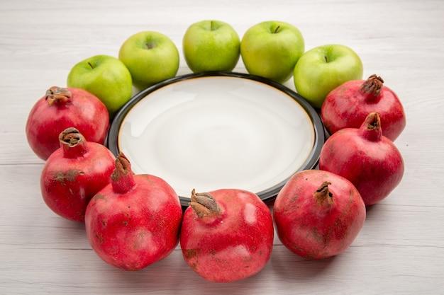 Vista inferior de maçãs verdes e romãs em torno de um prato redondo na mesa branca