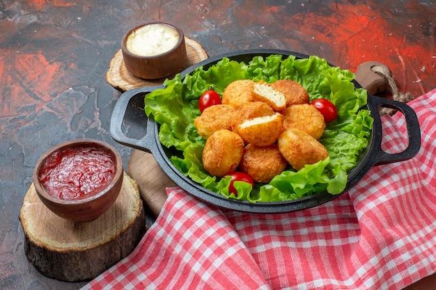 Vista inferior de nuggets de frango em tigelas de molho na placa de madeira, toalha de mesa vermelha sobre fundo vermelho escuro
