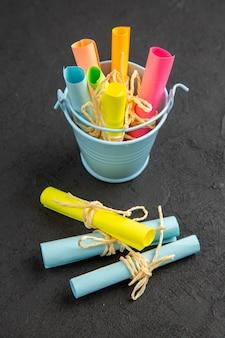 Vista inferior de papéis de notas coloridas enrolados em notas adesivas amarradas com corda em um pequeno balde na mesa preta