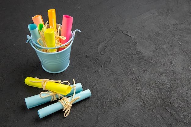 Vista inferior de papéis de notas coloridas enrolados em notas auto-adesivas amarradas com corda em um pequeno balde no espaço livre da mesa preta
