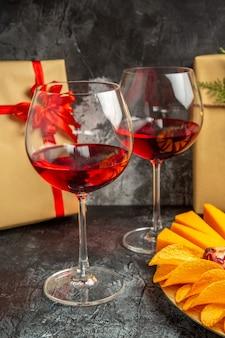 Vista inferior de pedaços de queijo, carne, uvas e romã em uma taça oval de vinho e presentes de natal no escuro