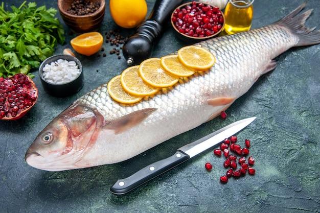 Vista inferior de peixe fresco com faca de rodelas de limão na mesa da cozinha