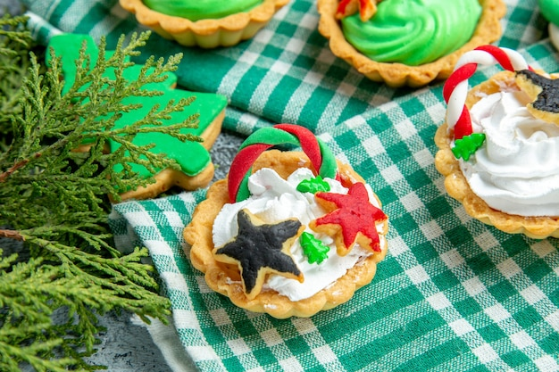 Vista inferior de pequenas tortas de natal em ramos de pinho na toalha de mesa na mesa cinza