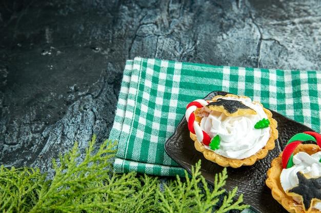 Vista inferior de pequenas tortas de natal em uma placa preta na toalha de mesa verde na mesa cinza