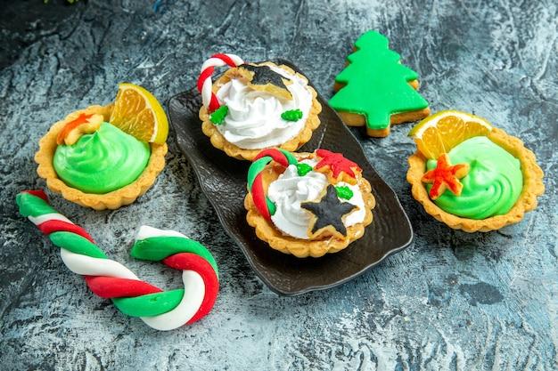 Vista inferior de pequenas tortas de natal na placa preta, doces de natal e biscoitos na mesa cinza