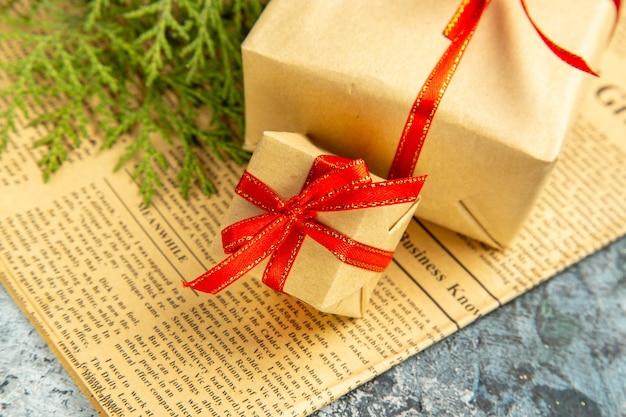 Vista inferior de pequenos presentes amarrados com fita vermelha no jornal no escuro