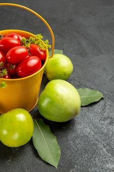 Vista inferior de perto balde amarelo cheio de tomates cereja e flores de endro cercado de tomates verdes em fundo escuro