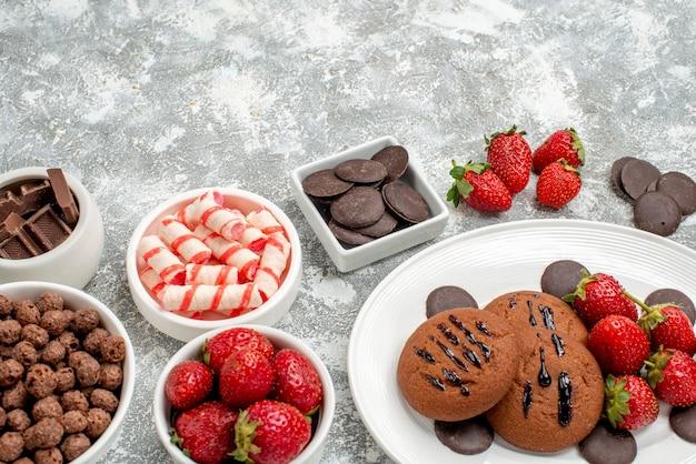 Vista inferior de perto biscoitos morangos e chocolates redondos no prato oval tigelas com doces, morangos e chocolates cereais na mesa cinza-esbranquiçada
