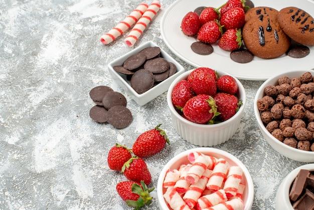 Vista inferior de perto cookies, morangos e chocolates redondos no prato oval branco, tigelas com doces, morangos, chocolates, cereais no lado direito da mesa cinza-esbranquiçada com espaço livre