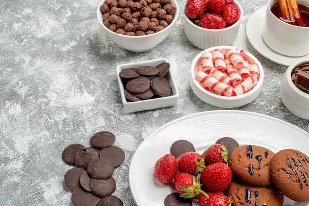Vista inferior de perto cookies, morangos e chocolates redondos no prato oval taças com doces, morangos, chocolates, cereais e chá de canela na mesa branco-acinzentada