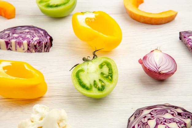 Vista inferior de perto corte legumes repolho roxo couve-flor pimentão amarelo tomate verde cebola roxa na superfície de madeira branca