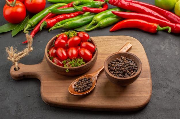 Vista inferior de perto pimentas vermelhas e verdes quentes e tomates com folhas de louro em tigelas com tomates cereja e pimenta preta e colher em uma tábua de cortar no fundo preto