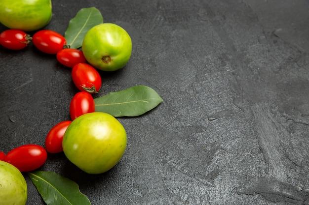 Vista inferior de perto tomates cereja tomates verdes e folhas de louro em fundo escuro