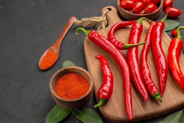 Vista inferior de perto uma tigela de tomate cereja, pimentão vermelho na tábua de cortar, deixa uma colher de pau e uma tigela de ketchup na mesa preta