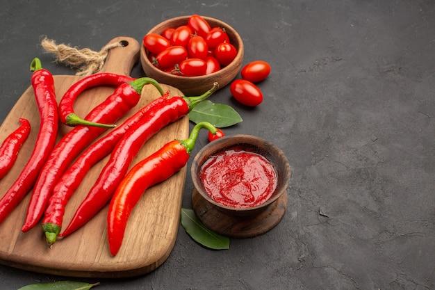Vista inferior de perto uma tigela de tomate cereja, pimentão vermelho na tábua de cortar folhas de louro e uma tigela de ketchup na mesa preta