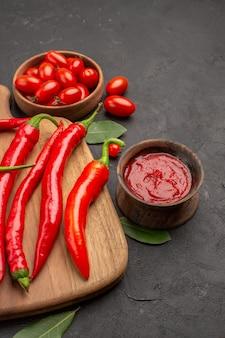Vista inferior de perto uma tigela de tomate cereja, pimentão vermelho quente na tábua de cortar folhas de louro e uma tigela de ketchup na mesa preta