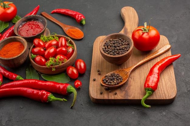 Vista inferior de perto uma tigela de tomates cereja pimentas vermelhas quentes folhas de louro e uma tigela de pimenta preta uma colher de pau um tomate uma pimenta vermelha na tábua de cortar no chão preto