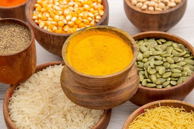Vista inferior de perto várias especiarias, açafrão-da-índia, pimenta-do-reino em pequenas tigelas, arroz, feijão e outras coisas na mesa cinza