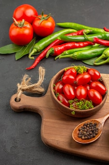 Vista inferior de pimentão vermelho e verde quente e tomate louro deixa uma tigela com tomate cereja e pimenta preta em uma colher em uma tábua no chão preto