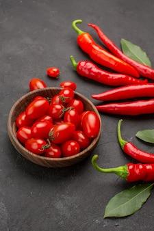 Vista inferior de pimentas vermelhas e folhas de pagamento e uma tigela de tomates cereja na mesa preta