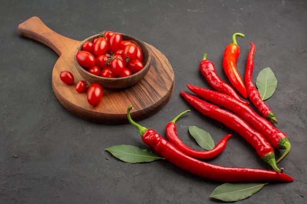 Vista inferior de pimentas vermelhas e folhas de pagamento e uma tigela de tomates cereja na tábua de cortar na mesa preta